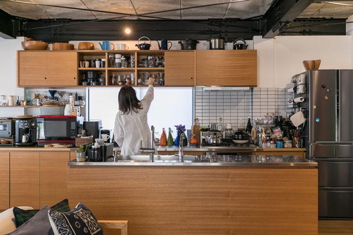 キッチンの吊り戸棚やアイランドキッチンの腰板は、白ラワン材の突板を使っている。キッチンの天板は熱い鍋などもそのまま置けるステンレスに。「ヒースタイルを使ってみたいとも思いましたが、そこは敢えて引き算のデザインにして、シンプルな白のタイルにしました」