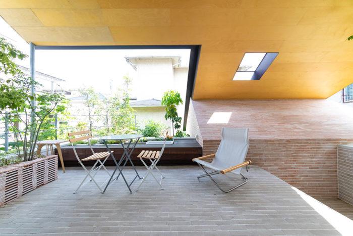 大きな屋根の下に登場したアウトドアリビングは2階に位置する。隣家の緑も借景に一役。