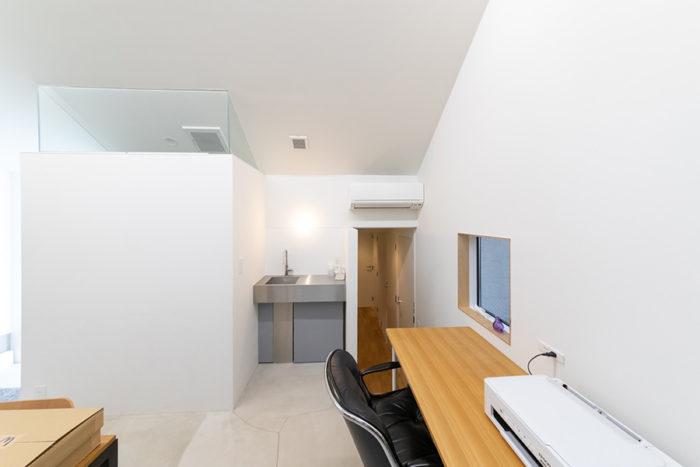 オフィスにはミニキッチンやトイレ(左)も完備。右奥の階段から住居スペースへ。