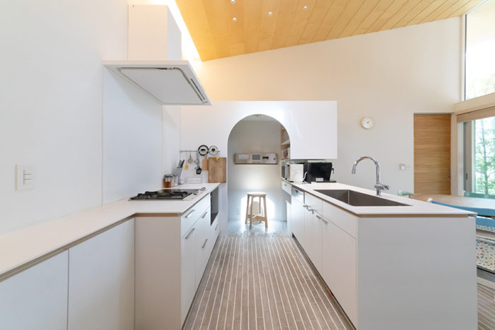 真っ白でシンプルなキッチン。カーブを描いた入り口がかわいらしいキッチンボックスには、冷蔵庫をはじめとした家電から食材、食器、給湯器類のリモコンまで収納。天窓からの光がスツールを美しく照らしていた。