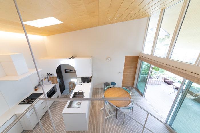 2.5階のリビングから2階を見る。床の白化粧タイルと天井までの大きな開口が明るい空間を印象づける。