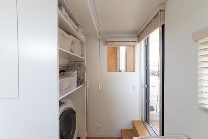 洗面室から洗濯機などが見えないように置いた。右側のドアから大屋根の下に出ることができ、物干しスペースに。