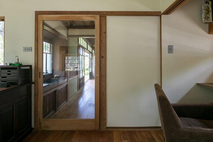 """廊下との境界にも、""""隅丸""""の古建具を。ガラス越しに廊下の奥まで見通せる。"""