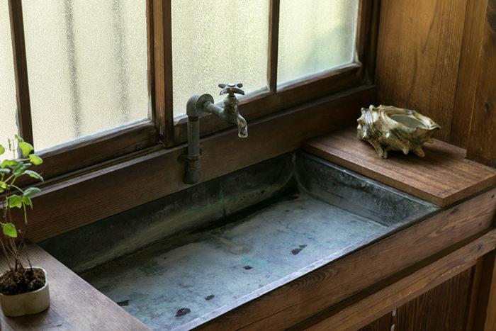 廊下にある手洗い場は既存のまま。水栓金具や金属製の流し台がレトロな雰囲気。