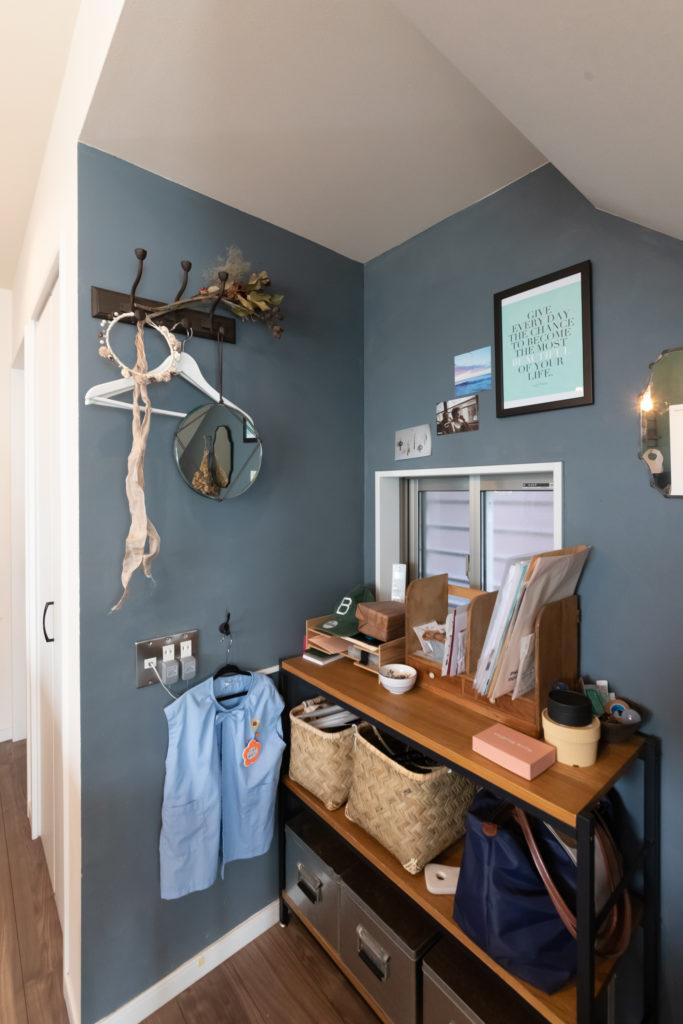 階段下の収納スペースは扉を設けず、オープンに。濃いブルーをDIYで塗り、外出時に必要なものを置いている。