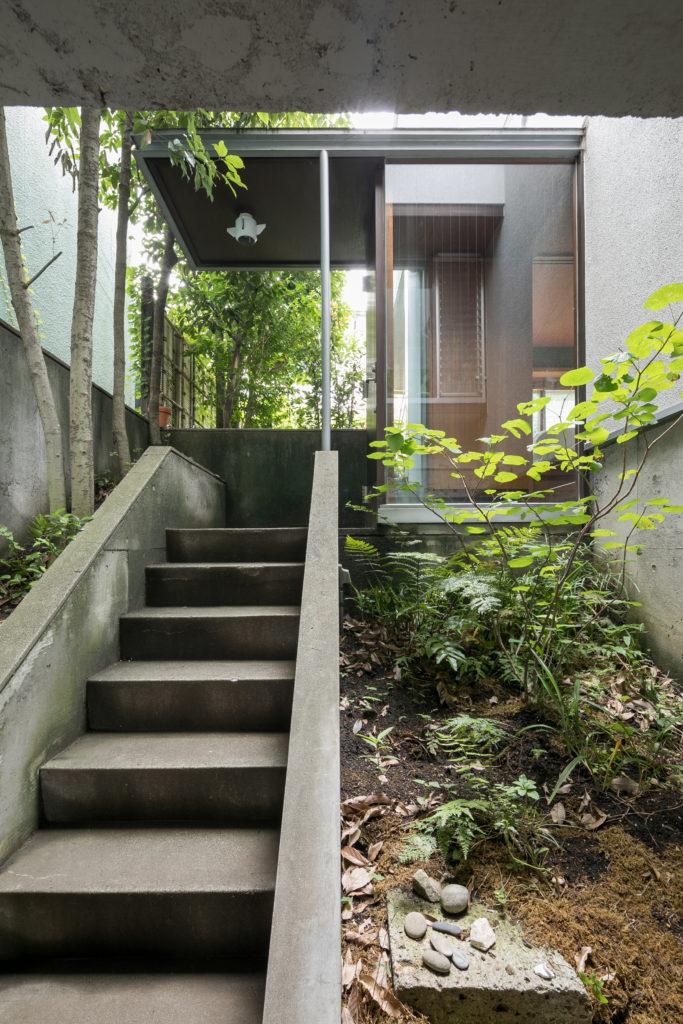 エントランスまでのアプローチ脇にも植栽スペースがある。右手には仕事部屋がある。