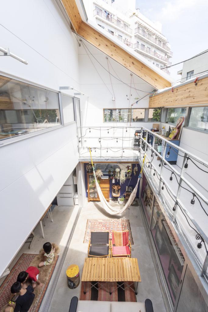 2階から外部につくられたリビングを見る。左にダイニングキッチン。