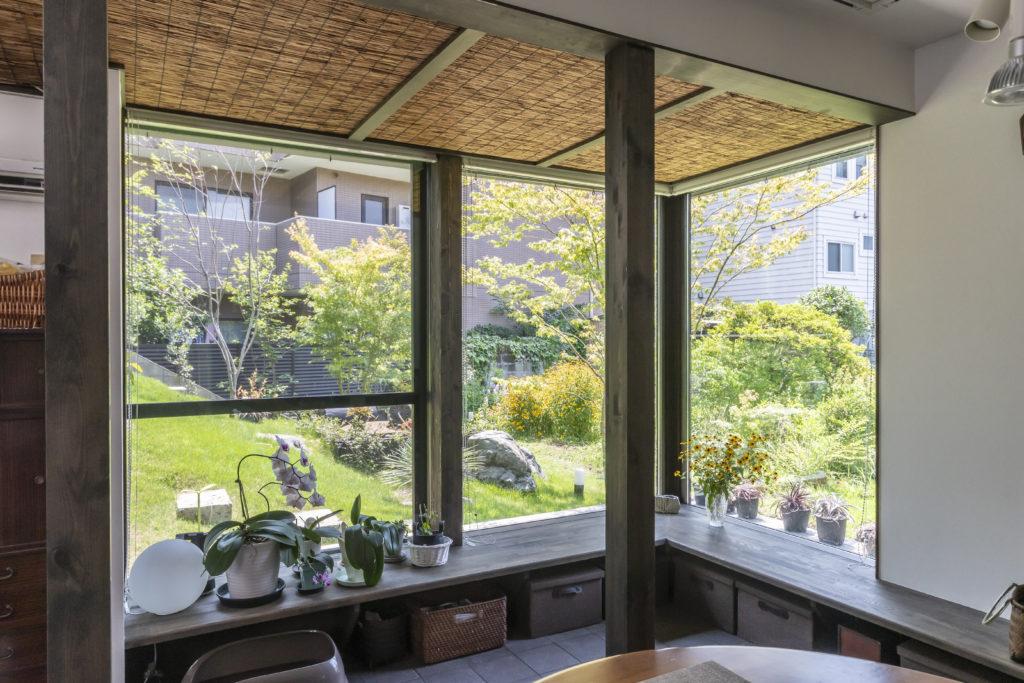 親世帯1階のコーナーにつくられたベンチ付近から庭を見る。玄関からこのコーナー部分までタイルの床と簾天井が続く。手前の柱は構造的な役割およびDK部分とベンチ付近のスペースを分節する役割をもたせられている。