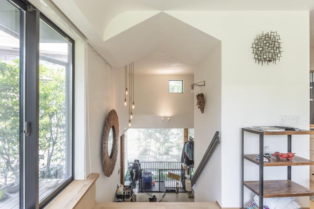 子世帯のリビングから玄関を見る。家形の空間の部分に幅広の階段がつくられている。