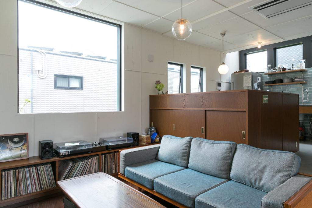 ウッドのキャビネットの中にダイニングスペースがある。ソファのブルーとキッチンのタイルのブルーが、白とウッドの空間に映える。