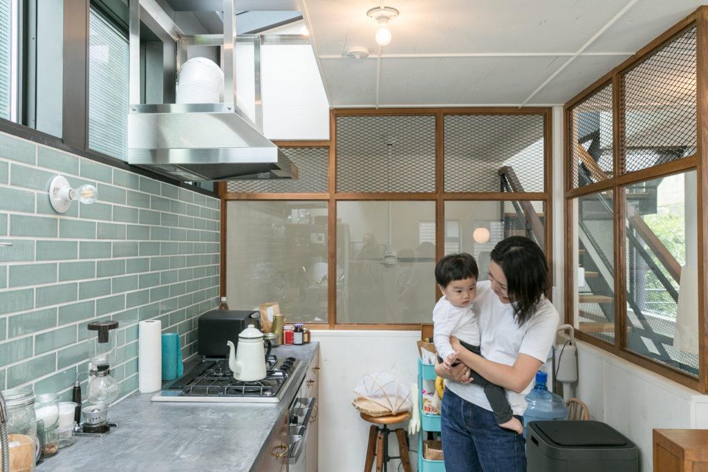 大きな吹き抜けの天窓から明るい光が差し込むキッチン。カウンターは防水効果の高いモールテックスで仕上げている。釉薬のかかった淡いターコイズ・ブルーのタイルが美しい。