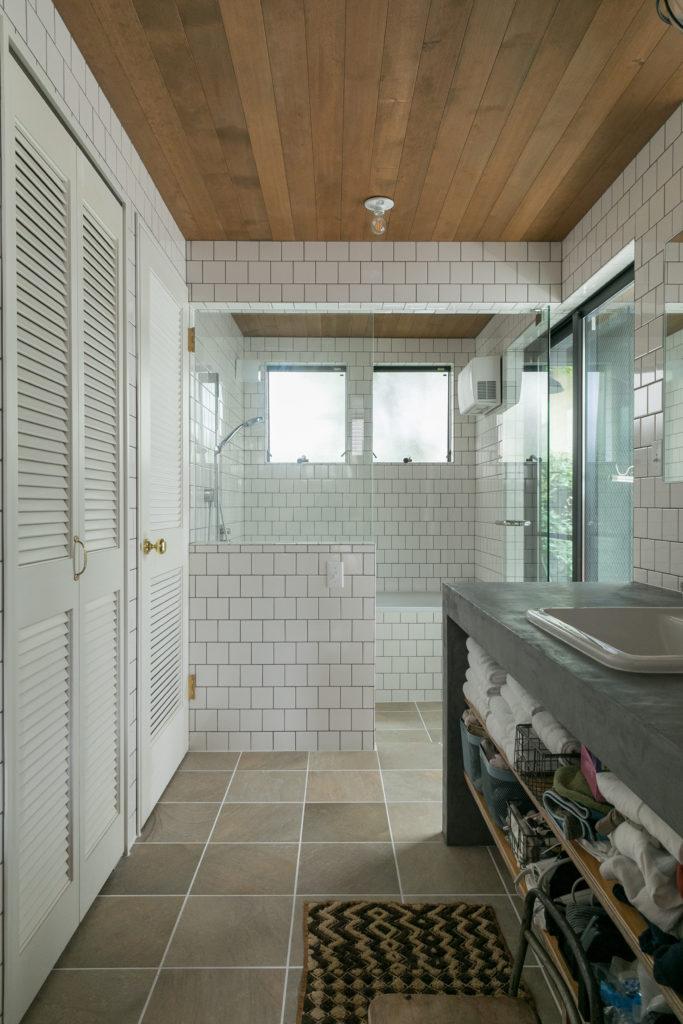 1階のバスルームも気持ちの良い光がたっぷりと差し込む。洗面台はモールテックス。ルーバーの収納扉とドアには真鍮の把手を。