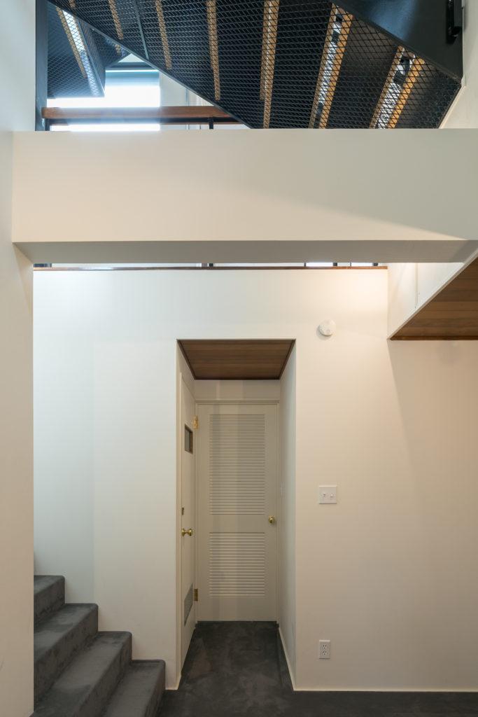 階段室は2階まで吹き抜けになっている。エキスパンドメタル越しに光が1階まで差し込む。