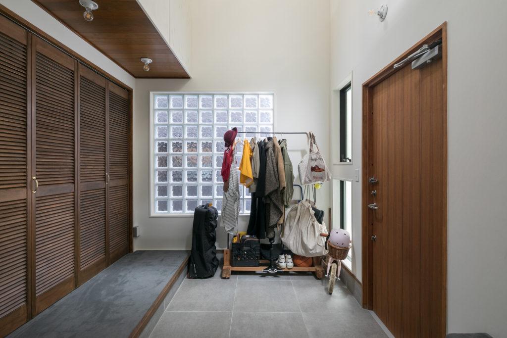 ガラスブロックから明るい光が差し込む広々とした1階エントランス。グレーのカーペットと、大判のグレーのタイルの組み合わせ。