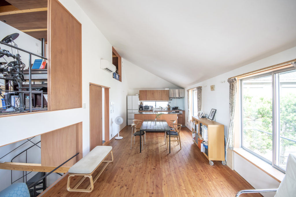 リビング側からダイニングとキッチンを見る。左上が趣味室でその下が玄関ホール。素材感にこだわったH夫妻はこの空間の壁天井に砂漆喰、フローリングには「木を感じられる」材を選択した。