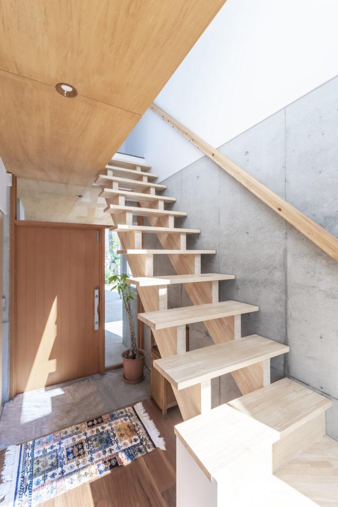 この家では玄関部分だけが1階にある。存在感のある木の階段も印象的。