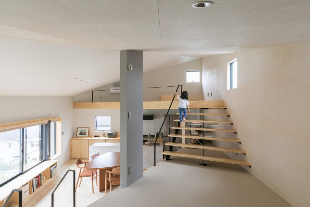 リビングからロフトに上がる階段は、幅広でゆったりした雰囲気に。透かし階段にしたことで、視線の抜けを確保した。中央の壁は、「あった方が落ち着く」というご主人の要望で設けた。
