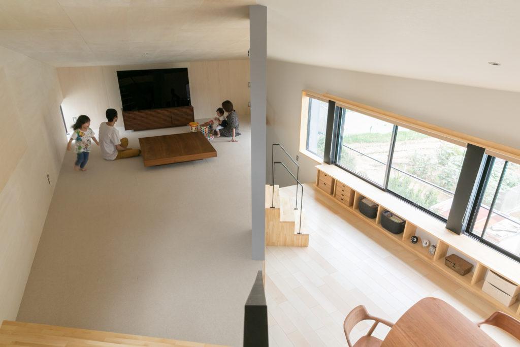 ダイニングの床はシカモアのフローリング、リビングの床は絨毯。リビングで床座でくつろぐのが、Kさん一家の団らんスタイル。ダイニングからリビングに上がる階段は可動式で、気分によって置き場所を変えられる。
