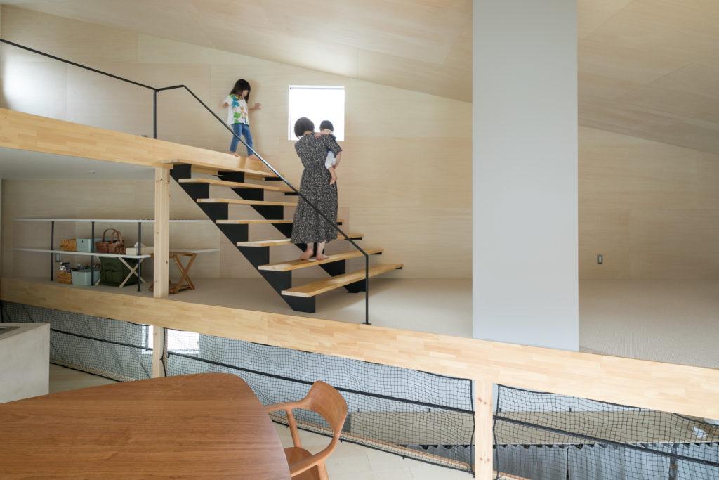 ロフトに上がる階段の奥には食材を保管する棚をつくり、空間を有効活用。ダイニングとリビングの段差によって1階からロフトまでがひとつながりの空間となっているが、全館の空気を循環させる換気システムを取り入れているので、高低差による温度差は解消されている。