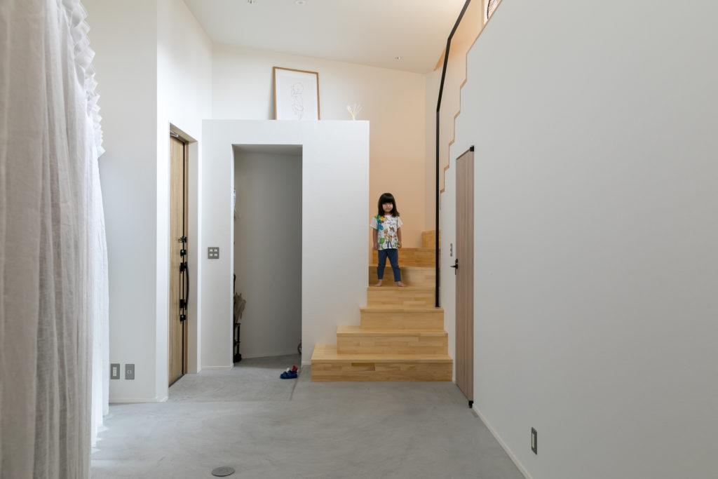 2階に上がる階段。階段から上は1階とは雰囲気が一転し、木の温もりを感じる空間になっている。玄関の脇にはシューズインクロークをつくったので、玄関周りはいつもスッキリ。