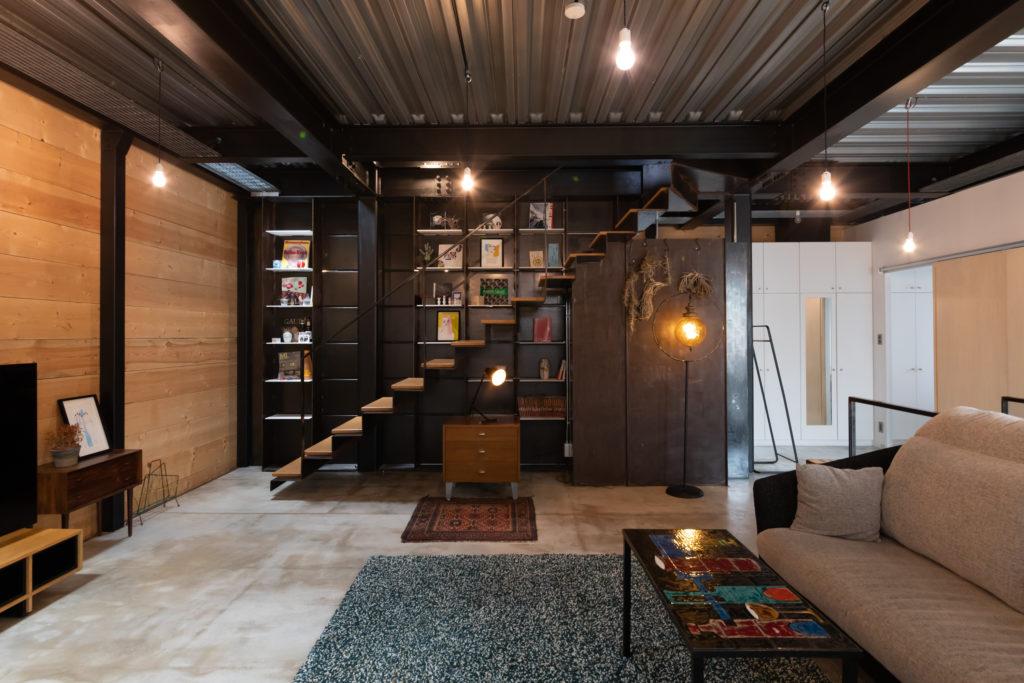 ギャラリーのような設えの階段。「階段下の右の鉄板はサンポールで錆びさせました。いい感じに錆びたところで錆止めを塗りました」 これは弓恵さんのDIYだそう。「妻はこの家に住んでからDIYをするようになりました」