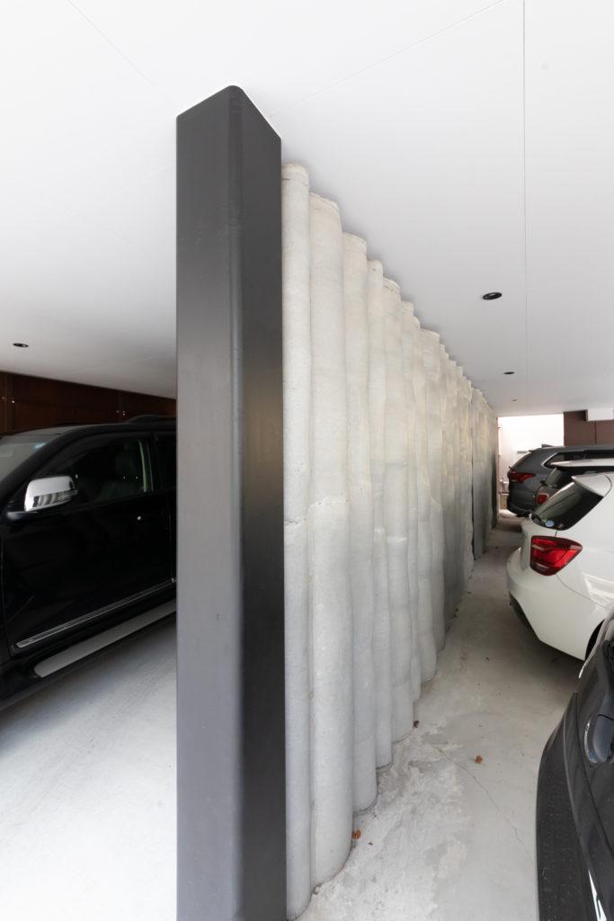 「一般的なコンクリートの壁はコンパネで平らに作りますが、この有機的な壁は麻袋にコンクリートを流し入れて作る海野さんオリジナルの『URC』です。コンパネを使うより安価で、造形がおもしろく、強度も高いです」