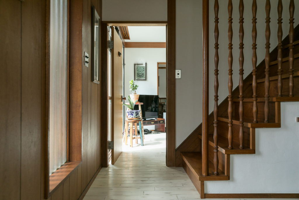 玄関からリビングを見る。すりガラスに差し込む光が玄関スペースを自然な明るさに。右手に見える階段の木の格子が和モダンな雰囲気。