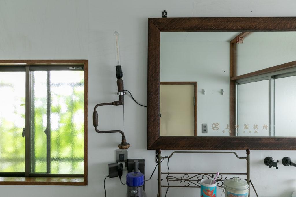 夫妻が洗面所に取り付けたのは、益子の骨董屋で見つけたという大きな鏡。鏡面に印刷された三桁の電話番号が歴史を感じさせる。