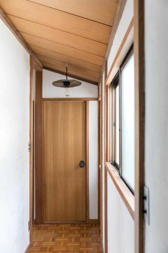 2階の廊下は屋根の形状を活かした勾配天井となっている。元々は砂壁だったが、大介さんが漆喰で白く塗り替えたことで雰囲気が大きく変わったという。奥に見えるのは、シンバルを加工したというユニークな照明。