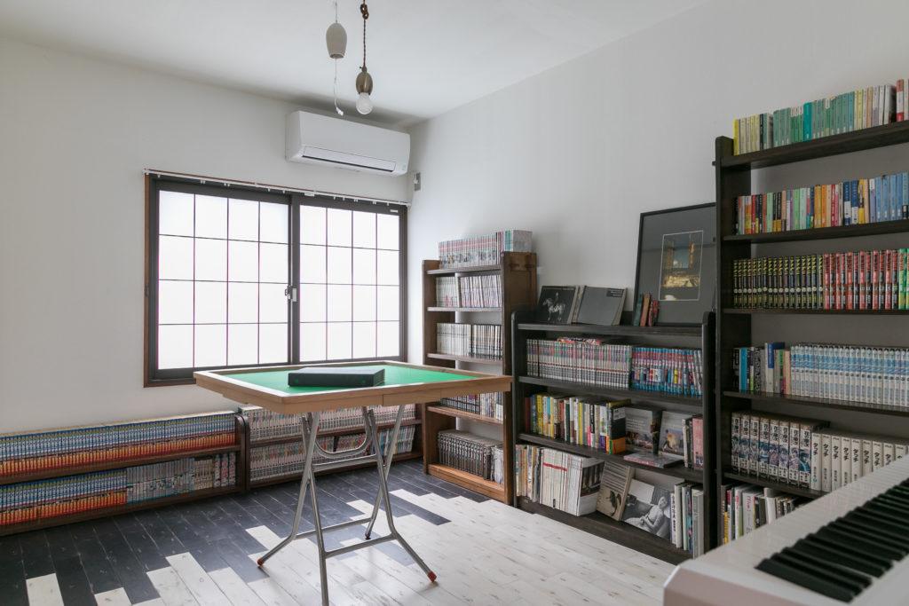 ご夫妻共通の趣味である麻雀の卓を中心に据えたプレイルーム。周りを大介さんの趣味の漫画がずらりと囲む。