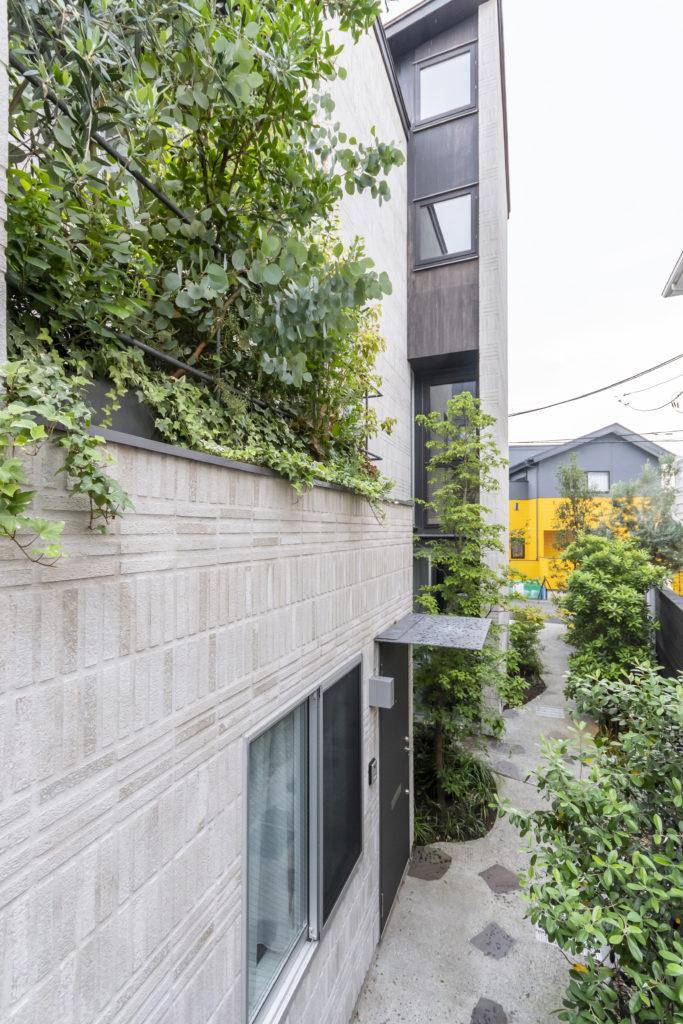 手前の1階が賃貸でその上がO邸の2階のテラス。通路に沿って緑が植えられている。