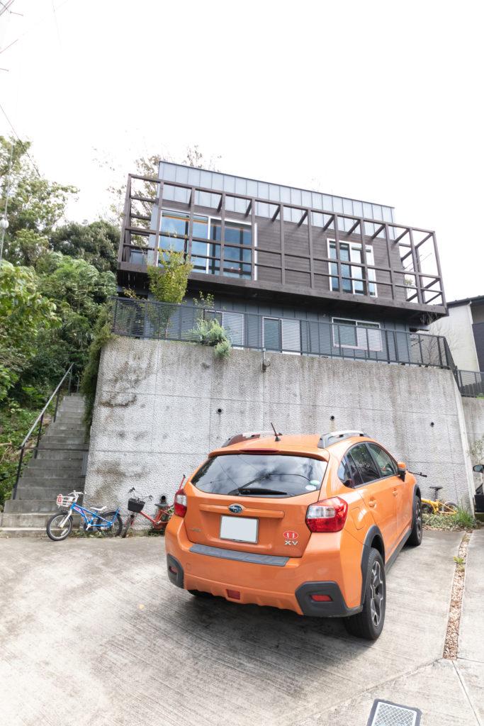 2階部分に設置した回廊と帯状に張った杉板で個性的な外観に。斜面に建つため、高い土台が必要だった。