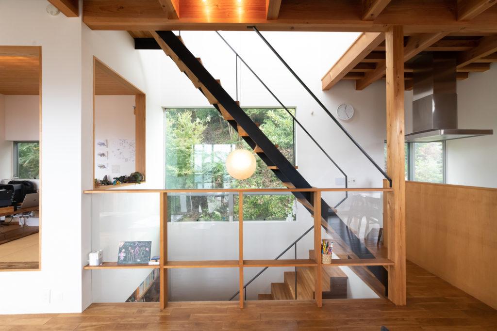 裏の山林が見える階段脇の窓。建築家・伊東豊雄デザインの照明が、リビングから見たときにちょうど中央にくるよう考えられている。