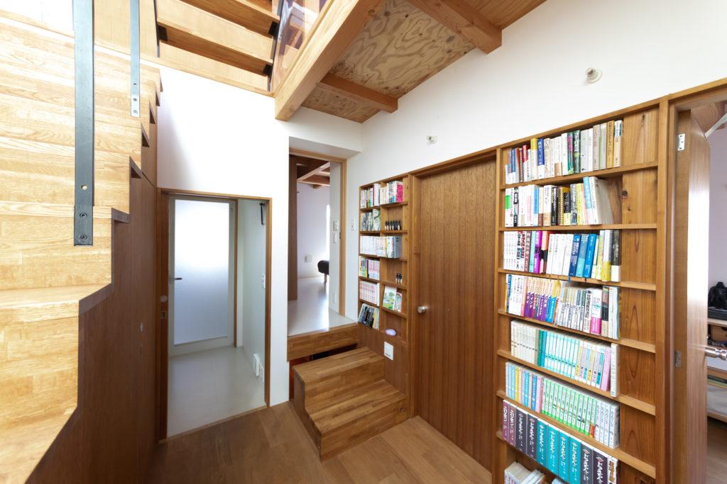 壁をくり抜いて造作した本棚。本棚の右奥が子供部屋。奥の寝室の下が地下収納で、階段をずらして入る。