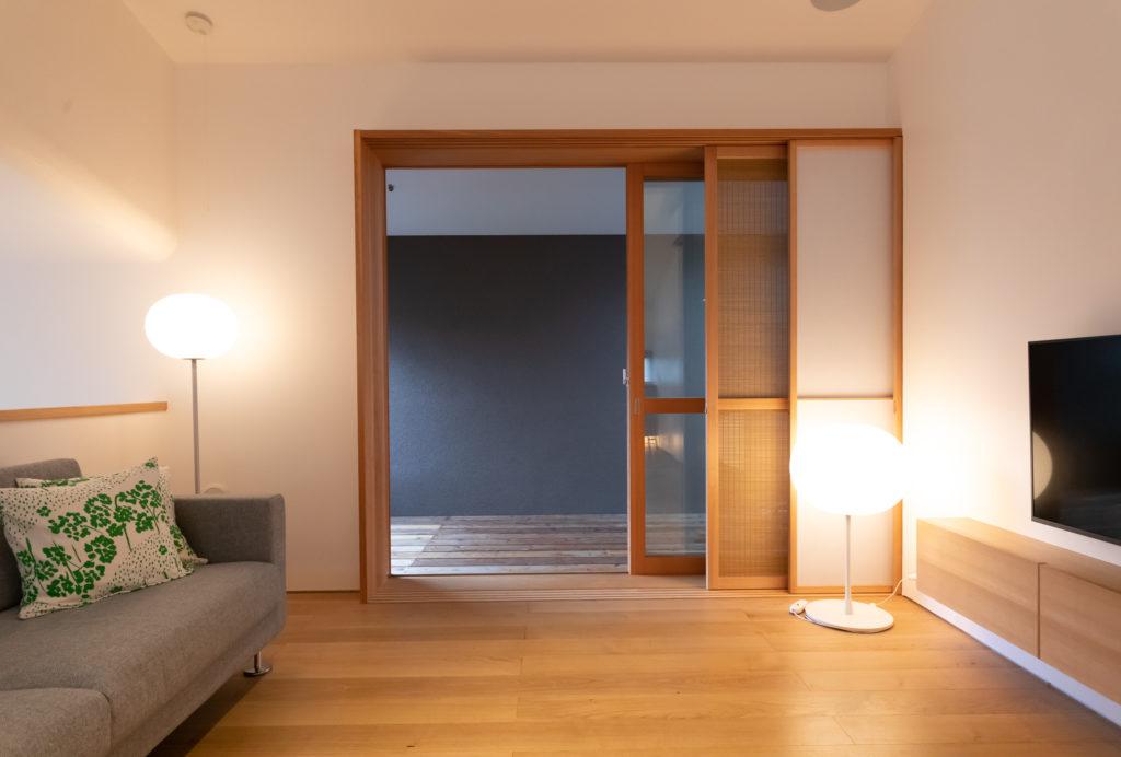 リビングからつながった半室内的なテラスは、日本家屋の広縁のようでもあり、色々な使い方ができる。テラスにはサイドと屋根に開口があり、光と風が通り抜ける。仕切りには造作した木枠のガラス窓、簾、障子の引き戸を。