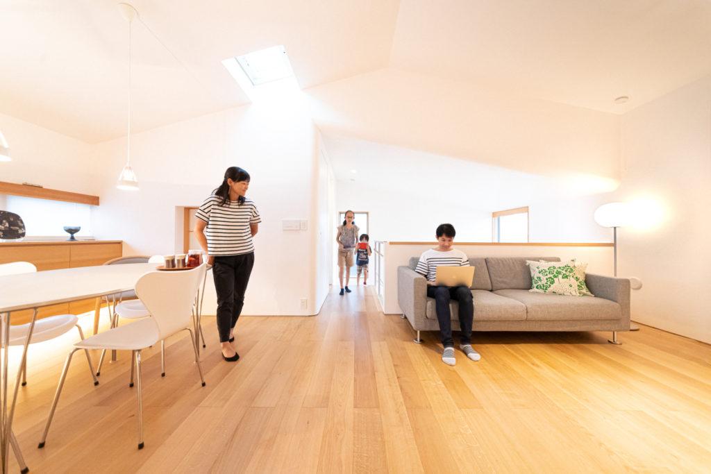 ナラの床材が気持ちいいリビングダイニング。漆喰の壁が光の反射を受けて陰影を出す。ジャスパー・モリソンのソファーの置き場所も考えて設計。