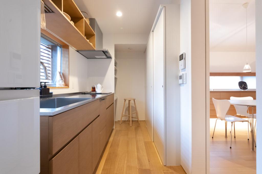 仕切りを設けてあえて独立させたキッチン。キッチン台やオープンシェルフはアッシュで造作。手前にはパントリーがあり、収納もたっぷり。