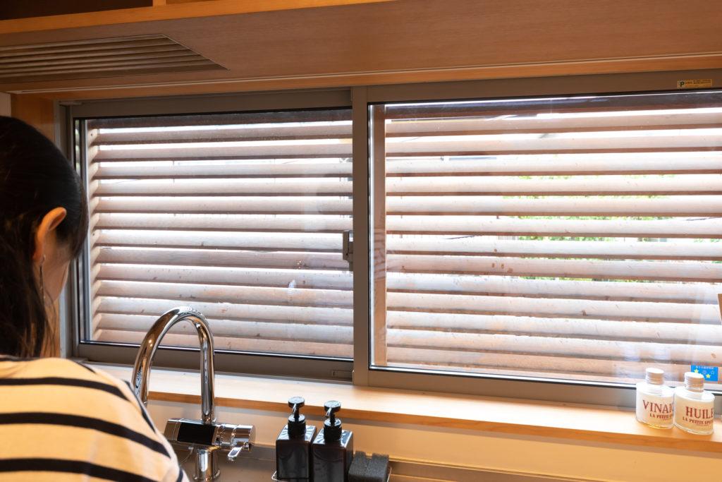 隣家の視線を避けるため、窓の外にルーバーを設置。吊り棚の底面は、洗いものをそのまま置くことができるよう工夫されている。
