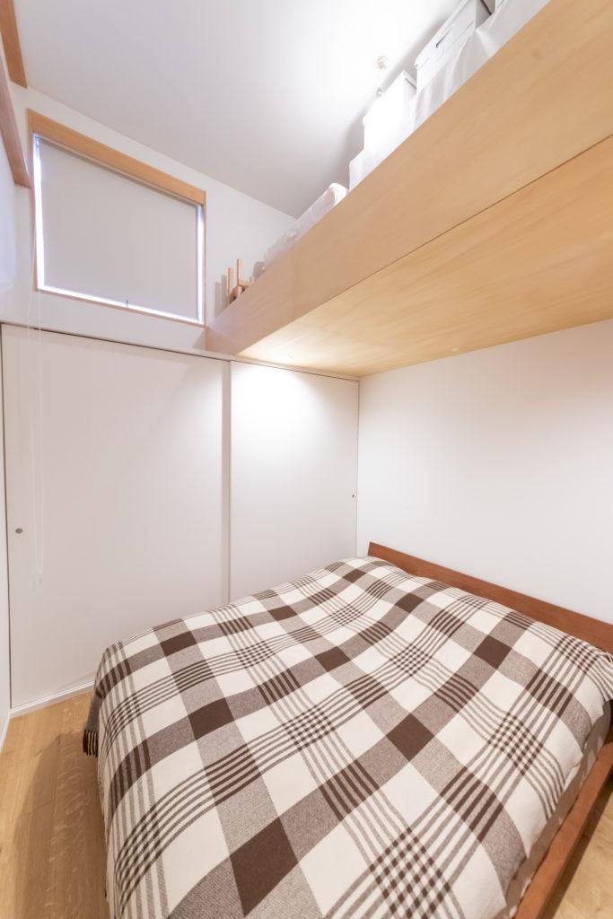 1階の主寝室は天井を2フロア分の高さにして、ハシゴであがるロフトを設けた。2階リビングと接する壁には、障子の窓も設けている。