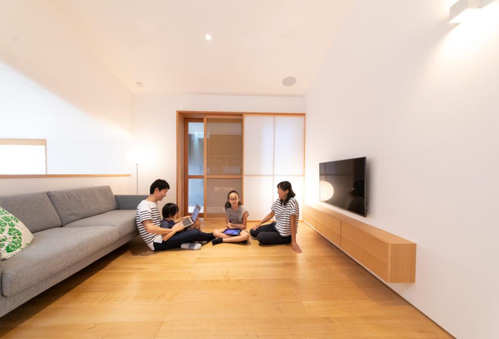 リビングで寛ぐことも多いご一家。スピーカーは埋め込みに、テレビは壁付けにしてすっきりと。テレビ下の収納は、壁の向こう側のパントリーの空間を活用して奥行きを取り、リビング側はすっきりと薄いデザインに。