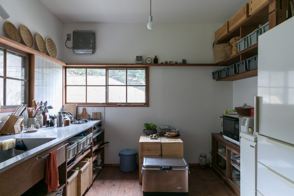 キッチンの棚の下段はリンゴ箱にキャスターをDIYでつけた。引き出しにはプラスティックのケースも。「プラスティックは素材的に最初はどうかなと思ったのですが、使ってみるとそれほど違和感ありませんでした。左側のはFOUND MUJIで、右の棚の収納に使っているのは近くのケーキ屋さんが移転するときにいただきました」。真ん中のコールマンのクーラーボックスの中にはぬか床が!