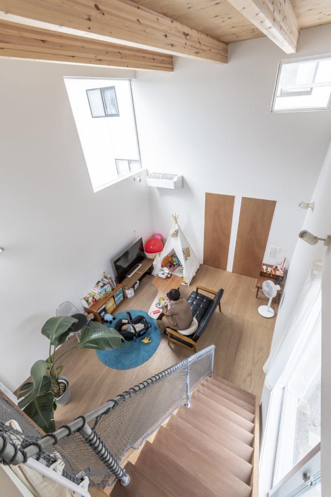 サンルーム側からリビングを見下ろす。奥の木の扉を開けると左が書斎で、右はベッドルームに至る階段がある。