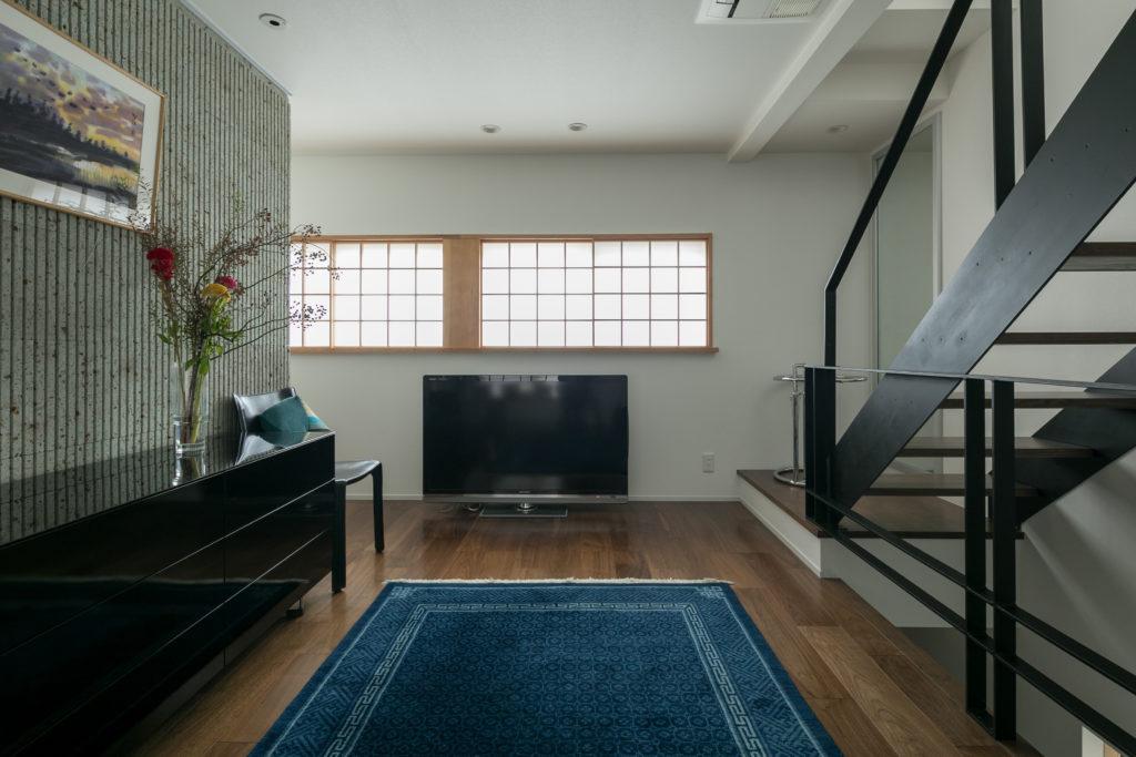 2階のリビングはベッドルームも兼ねている。写真左が大谷石の壁。溝加工されているため、モダンな印象だ。