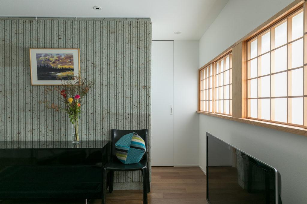 大谷石の壁の向こうに収納や洗面室、浴室などの水回りが配されている。