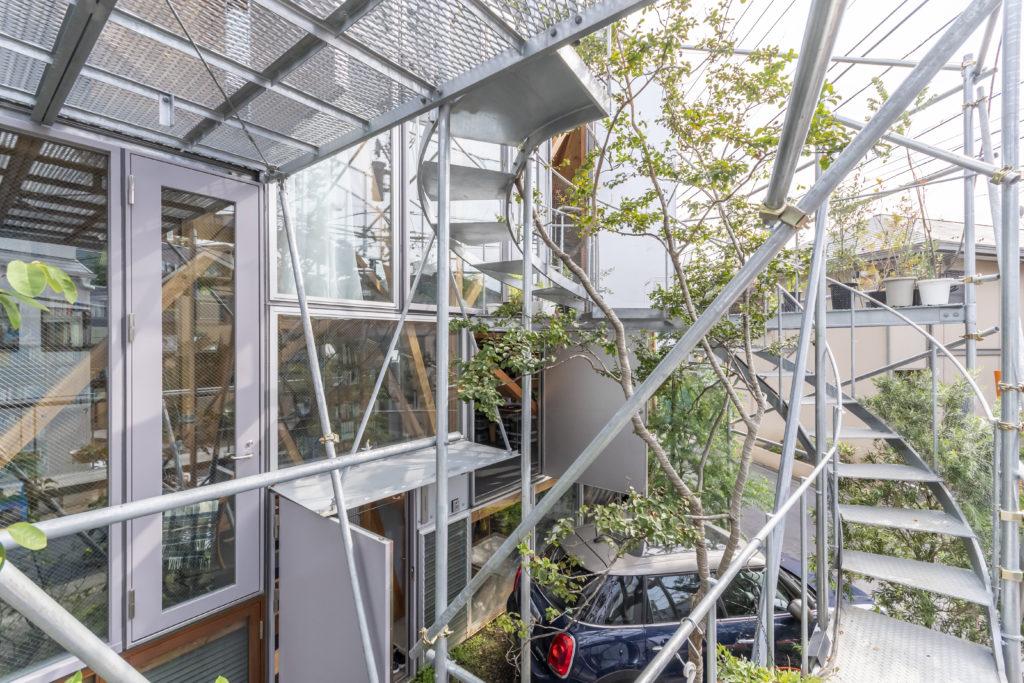 反時計回りに階段が地上の1層目につくられた書斎の前のテラスを経て最上層へのテラスへと至る。外構部分の緑とスチールがプライバシーを守るバッファ的な役割も担っている。