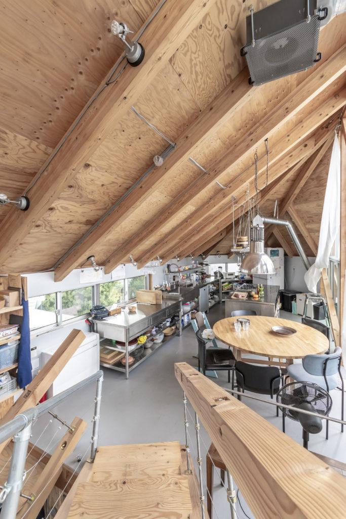 ダイニングとキッチンを見る。天井は骨組みだけでなく配線なども表に出して視覚的にわかるようにしている。