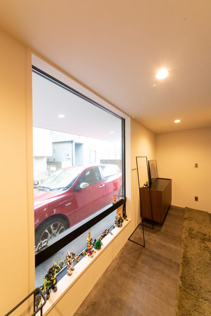 上がり框のないフラットな玄関ホール。墨を混ぜたモルタルがシックな印象。車が眺められるギャラリー風ガレージ。