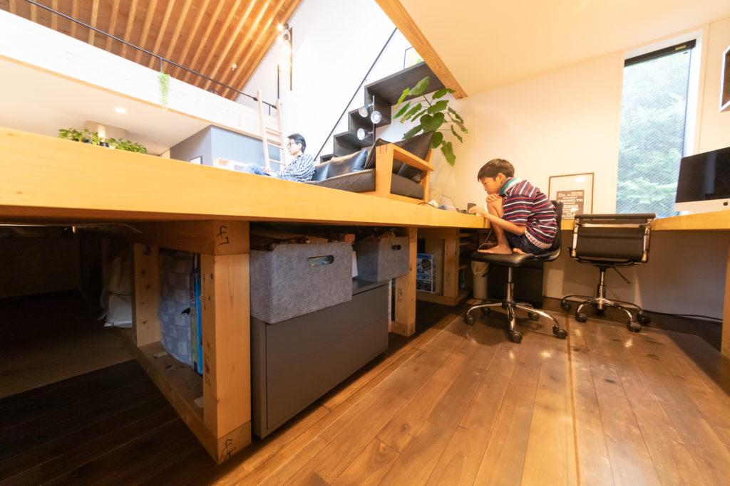 リビングの下はすべて収納になっている。使用頻度が少ないものは奥に入れるなど工夫が見られる。床座はデスクスペースにもなる。