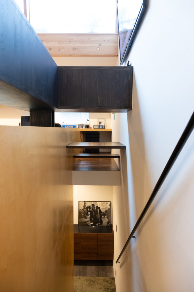 2階から1階の玄関ホールを見下ろす。「手で触るところは黒にしてもらった」と、アクセントカラーは黒をリクエストした奥さま。上部の黒い収納は、安全面を考えた柵との兼用。