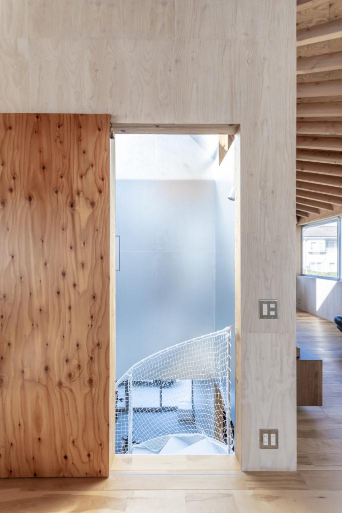 素材感のある戸と素材感の薄い階段室壁面とのコントラストが面白い。